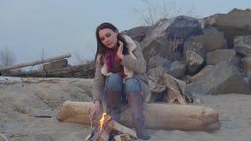 Jonge vrouwenzitting dichtbij de brand in de avond stock videobeelden