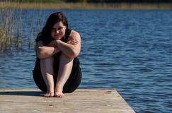 Jonge Vrouwenzitting die op de Pier mediteren royalty-vrije stock foto's