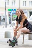 Jonge vrouwenzitting die rolschaatsen dragen royalty-vrije stock afbeeldingen