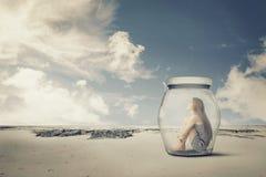 Jonge vrouwenzitting in een kruik in de woestijn Het concept van de eenzaamheidsuitloper Royalty-vrije Stock Foto's