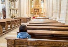 Jonge vrouwenzitting in een lege kathedraal royalty-vrije stock fotografie