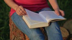 Jonge vrouwenzitting in een park en lezing een boek stock video