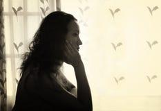 Jonge vrouwenzitting en het denken dichtbij helder vensterlicht zwart-wit gefiltreerd beeld stock foto's