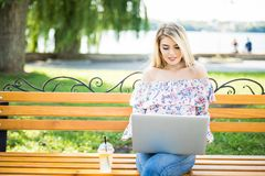 Jonge vrouwenzitting en het ontspannen op de Parkbank en gebruikend laptop Royalty-vrije Stock Fotografie