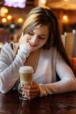 Jonge vrouwenzitting in koffie royalty-vrije stock foto's