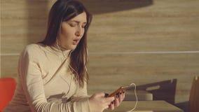 Jonge vrouwenzitting in koffie met hoofdtelefoons en het luisteren aan muziek stock footage