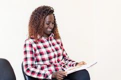 Jonge vrouwenzitting met in hand tijdschrift Stock Foto