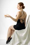 Jonge vrouwenzitting met wijnglas, helft-draai royalty-vrije stock fotografie