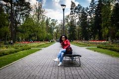 Jonge vrouwenzitting op bank in een park royalty-vrije stock foto's