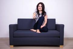 Jonge vrouwenzitting op bank en het letten op TV thuis Stock Afbeeldingen