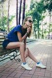 Jonge vrouwenzitting op bank in park, het denken Stock Foto's