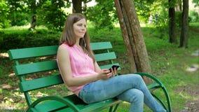 Jonge vrouwenzitting op de bank in het park, die smartphone met oortelefoons gebruiken Mooi Meisje die smartphone gebruiken met stock footage