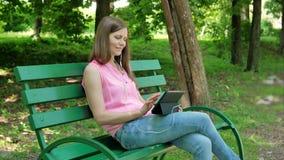 Jonge vrouwenzitting op de bank in het park, die tabletcomputer met oortelefoons met behulp van Mooi Meisje die tabletcomputer me stock footage