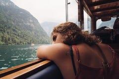 Jonge vrouwenzitting op de boot door mooi meer royalty-vrije stock foto