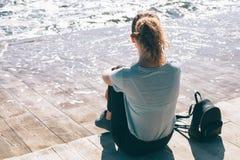 Jonge vrouwenzitting op de dijk naast kleine rugzak stock fotografie