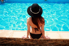 Jonge vrouwenzitting op de richel van de pool stock foto's