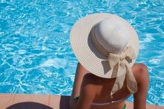 Jonge vrouwenzitting op de richel van de pool royalty-vrije stock afbeeldingen