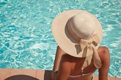 Jonge vrouwenzitting op de richel van de pool stock foto