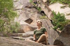 Jonge vrouwenzitting op de rots in wilde reserve Royalty-vrije Stock Fotografie