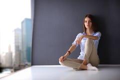 Jonge vrouwenzitting op de vloer dichtbij donkere muur Royalty-vrije Stock Afbeelding