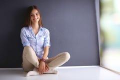Jonge vrouwenzitting op de vloer dichtbij donkere muur royalty-vrije stock foto's