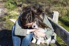 Jonge vrouwenzitting op een bank die haar witte hond koesteren royalty-vrije stock foto's