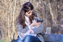 Jonge vrouwenzitting op een bank die haar witte hond koesteren royalty-vrije stock afbeeldingen