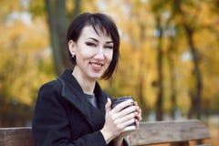 Jonge vrouwenzitting op een een bank en het drinken koffie, de herfstseizoen, stadspark, gele bladeren Stock Afbeeldingen