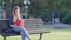 Jonge vrouwenzitting op een een bericht ontvangen en bank die, die rond eruit zien stock footage