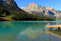 Jonge vrouwenzitting op een pijler in Emerald Lake, Yoho National Par Royalty-vrije Stock Afbeelding