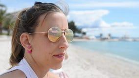 Jonge vrouwenzitting op een strand die binnen aan de afstand kijken stock footage