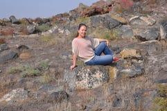 Jonge vrouwenzitting op grijze stenen Stock Fotografie