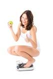 Jonge vrouwenzitting op haar lenden op een schaal Stock Fotografie