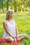 Jonge vrouwenzitting op het gras Royalty-vrije Stock Foto