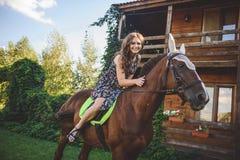 Jonge vrouwenzitting op horseback, gang in de aard Royalty-vrije Stock Afbeelding