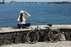 Jonge vrouwenzitting op kade in Spanje Stock Afbeelding