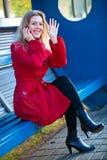 Jonge vrouwenzitting op posteinde stock foto