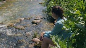 Jonge vrouwenzitting op rivierkust terwijl de zomertrekking Reis en toerisme stock videobeelden