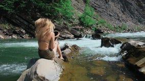 Jonge vrouwenzitting op rotsen op de bank van een bergrivier in Zwitserland stijgt zijn hoed op en spreidt zijn lang haar uit stock video