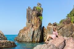 Jonge vrouwenzitting op rotsen overzeese kust Stock Foto