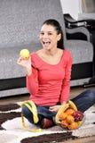 Jonge vrouwenzitting op tapijt en het genieten van van vruchten Royalty-vrije Stock Fotografie