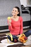 Jonge vrouwenzitting op tapijt en het genieten van van vruchten Royalty-vrije Stock Afbeelding