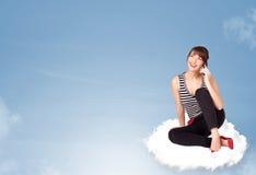 Jonge vrouwenzitting op wolk met exemplaarruimte Stock Foto
