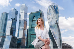 Jonge vrouwenzitting tegen bureaubuidings Royalty-vrije Stock Afbeelding