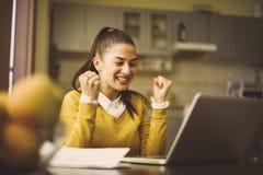 Jonge vrouwenzitting thuis en werkend aan laptop en rece stock fotografie