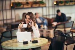 Jonge vrouwenzitting voor open laptop computer in koffiebar stock foto's