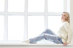 Jonge vrouwenzitting voor venster stock fotografie