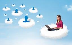 Jonge vrouwenzitting in wolk met laptop stock foto's