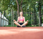 Jonge vrouwenzitting in yogapositie royalty-vrije stock afbeelding