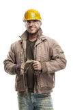 Jonge vuile Arbeidersmens die met Bouwvakkerhelm een het werkglo houden Royalty-vrije Stock Afbeelding